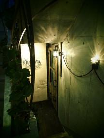 鉄の平棒と照明コードの描く曲線がお客様を入口へと誘導する
