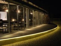 室内の曲面大壁を外へ表現するガラスのファサードと、同心円弧のテラス